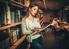 Jovem mulher em uma biblioteca de faculdade fotos de stock royalty free