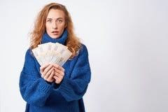 A jovem mulher em uma camiseta é surpreendida pelo dinheiro, em um backgr cinzento Fotos de Stock