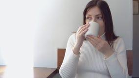 A jovem mulher em uma camiseta branca bebe o café em um café filme