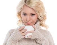 Jovem mulher em uma camiseta morna e em uma caneca em suas mãos imagem de stock royalty free