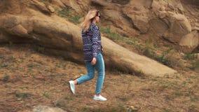 A jovem mulher em uma camiseta roxa do moderno alegre e em umas caminhadas na moda encurtadas das calças de brim nas montanhas, a vídeos de arquivo