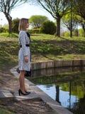 Jovem mulher em uma capa de chuva, calças justas, sapatas com saltos, com um saco de couro preto em suas mãos fotos de stock royalty free
