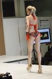 Jovem mulher em uma expo vermelha Moscou de Lingrie do desfile de moda do maiô Foto de Stock