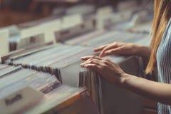 Jovem mulher em uma loja do registro de vinil imagem de stock