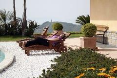 Jovem mulher em uma plataforma-cadeira na piscina Fotos de Stock Royalty Free
