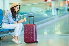 Jovem mulher em uma sala de estar do aeroporto que espera uma aterrissagem plana Mulher caucasiano com o smartphone na sala de es imagem de stock royalty free