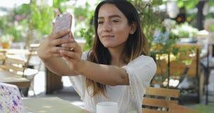 Jovem mulher em uma tabela do restaurante que toma um selfie vídeos de arquivo