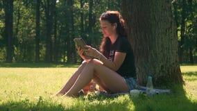 Jovem mulher em usos smartphone e tabuleta do parque video estoque