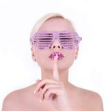 Jovem mulher em vidros do rosa do encanto com o dedo em seus bordos fotografia de stock royalty free