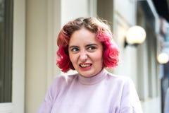 Jovem mulher emocional com cabelo ondulado cor-de-rosa com uma careta da negligência ou da raiva fotografia de stock royalty free