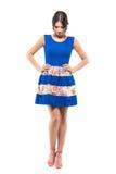 A jovem mulher emocional no vestido curto azul que olha para baixo com braços akimbo levanta imagens de stock royalty free
