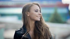 A jovem mulher encantador alegre é levantar, estando em uma rua no dia de verão, olhando a câmera, retrato do close-up filme