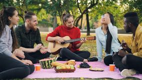 A jovem mulher encantador está jogando a guitarra que senta-se na cobertura com os amigos no piquenique, meninas e os indivíduos  vídeos de arquivo