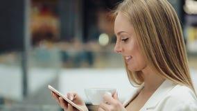 A jovem mulher encantador guarda o smartphone em umas mão e xícara de café em um outro assento no café filme