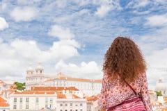 Jovem mulher encaracolado que admira a vista de um miradouro em Lisboa P Fotos de Stock Royalty Free