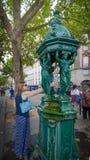 A jovem mulher enche acima a garrafa plástica em uma fonte de água pública em Paris Imagens de Stock