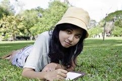 A jovem mulher encontra-se no prado verde do verão com livro Fotos de Stock Royalty Free