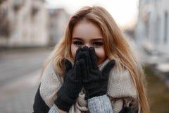 A jovem mulher engraçada de encantamento com olhos bonitos ri e cobre sua cara com suas mãos Menina à moda alegre foto de stock royalty free