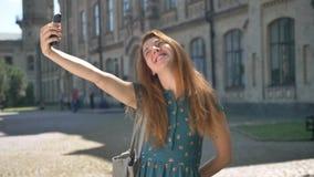 Jovem mulher engraçada do gengibre que faz expressões diferentes da cara e que sorri, tomando o selfie e a posição na rua video estoque