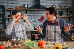 A jovem mulher engraçada senta-se na tabela com o marido na cozinha Cobriu os olhos com os tomates Homem surpreendido e querido s foto de stock royalty free