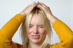 Jovem mulher enojado que risca sua cabeça Fotografia de Stock Royalty Free