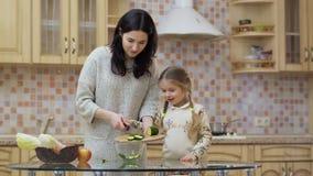 A jovem mulher ensina a menina cozinhar a salada vídeos de arquivo