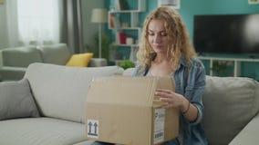 A jovem mulher entra em sua sala de visitas com pacote e abertura da caixa de cart?o dele