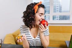 Jovem mulher entusiasmado alegre do retrato com cabelo cortado encaracolado que aprecia a maçã vermelha no apartamento moderno So fotografia de stock