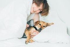A jovem mulher entusiasmado bonita e seu cão bonito da vira-lata são enganam ao redor, olhando a câmera ao encontrar-se coberto c imagens de stock royalty free