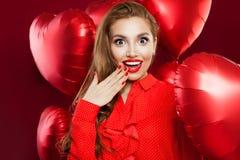 Jovem mulher entusiasmado com os balões vermelhos do coração A menina surpreendida com composição vermelha dos bordos, cabelo enc fotografia de stock royalty free