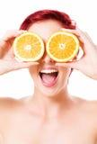 Jovem mulher entusiasmado que guarda laranjas sobre seus olhos Fotografia de Stock Royalty Free