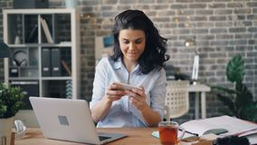Jovem mulher entusiasmado que joga o jogo na tela de toque do smartphone no trabalho filme