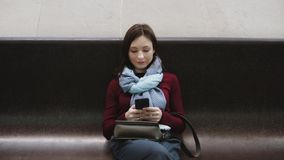 Jovem mulher entusiasmado que texting no smartphone que senta-se no banco de mármore no metro video estoque
