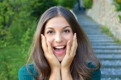 Jovem mulher entusiasmado surpreendida que guarda seu sorriso da exibição da cara Fotografia de Stock Royalty Free