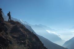 Jovem mulher ereta no monte e vista em montanhas Foto de Stock Royalty Free