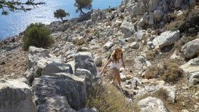 A jovem mulher escala uma rocha ao trekking fora video estoque