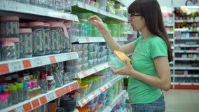 A jovem mulher escolhe a cesta de comida reusável video estoque