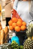 A jovem mulher escolhe laranjas frescas no supermercado imagens de stock