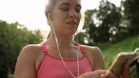 A jovem mulher escolhe a música para treinar vídeos de arquivo