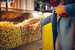A jovem mulher escolhe a pipoca no cinema Alimento e petiscos imagens de stock royalty free