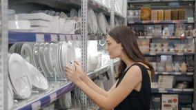A jovem mulher escolhe placas no cookware da loja, prato que escolhe pela menina elegante no supermercado Imagens de Stock Royalty Free