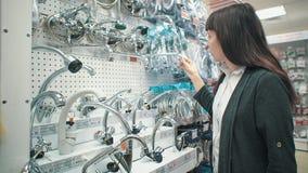 A jovem mulher escolhe a torneira de misturador na loja do autosservi?o filme