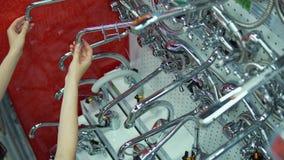 A jovem mulher escolhe a torneira de misturador na loja do autosservi?o video estoque