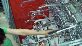 A jovem mulher escolhe a torneira de misturador na loja do autosservi?o vídeos de arquivo