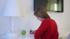 A jovem mulher escreve ao bloco de notas em uma tabela branca filme