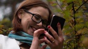 A jovem mulher escreve mensagens no telefone em um fundo das folhas amarelas ao andar no parque do outono Foto de Stock