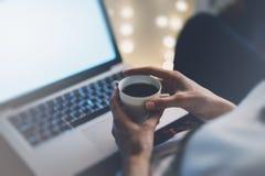 A jovem mulher escreve uma mensagem de texto no teclado do portátil com um monitor vazio da tela vazia ao ter o tempo para relaxa foto de stock royalty free