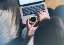 A jovem mulher escreve uma mensagem de texto no teclado do portátil com um monitor vazio da tela vazia ao ter o tempo da recreaçã fotografia de stock royalty free