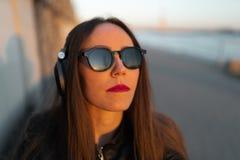 A jovem mulher escuta a música em fones de ouvido fechados através de seu telefone que veste um casaco de cabedal e calças de  fotos de stock royalty free