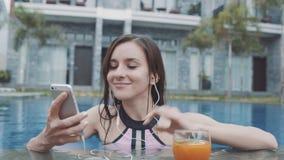 A jovem mulher escuta música nos fones de ouvido do smarthone na associação com coctail vídeos de arquivo